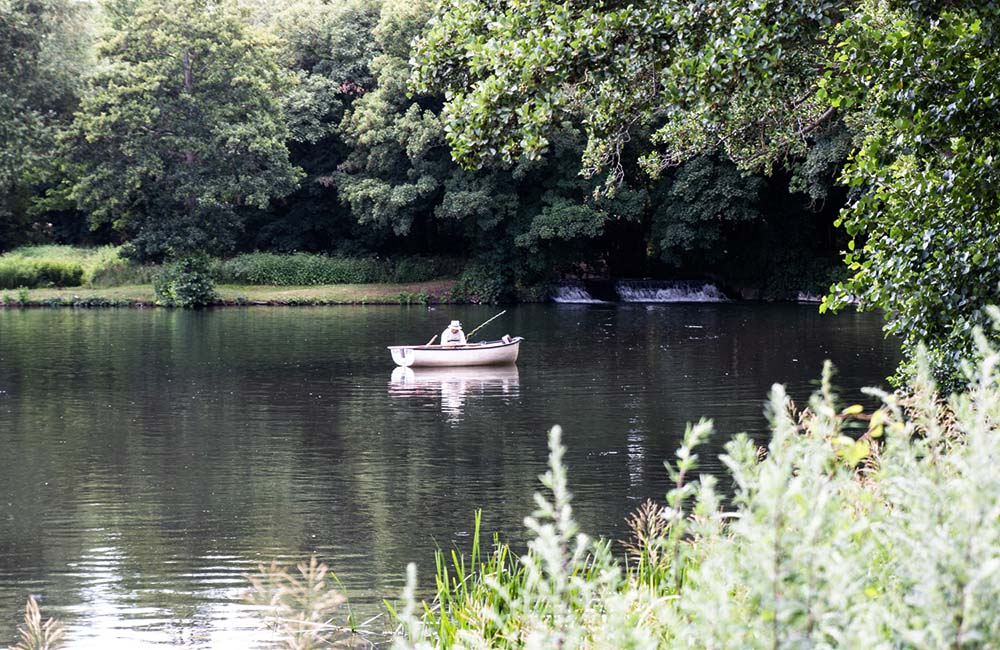 Man in small boat fishing on the lake at Lullingstone Castle