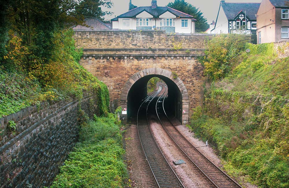 View of arched tunnel over train tracks with bridge above
