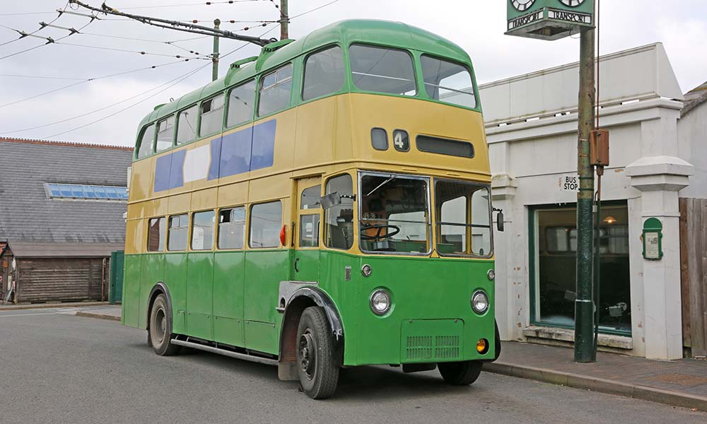 Vintage green double decker bus by town clock