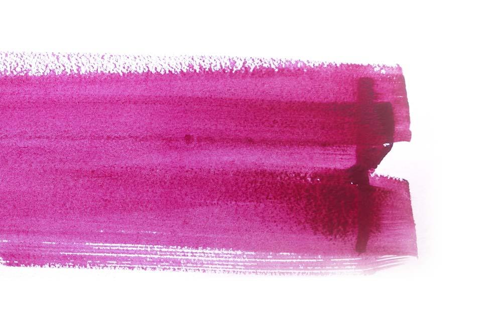 Brush stroke of magenta watercolour paint on white