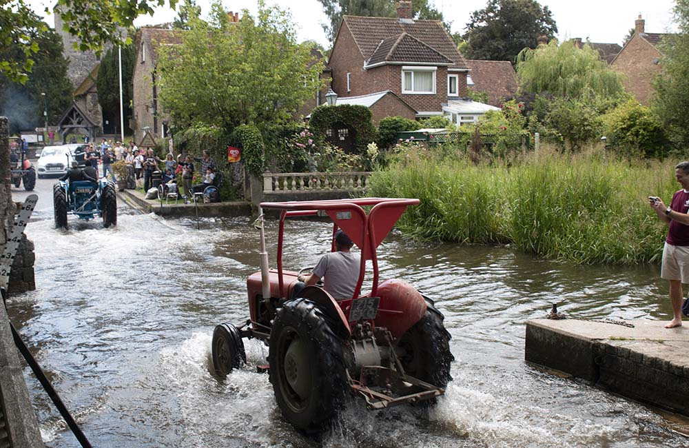 Vintage tractors driving through the ford at Eynsford
