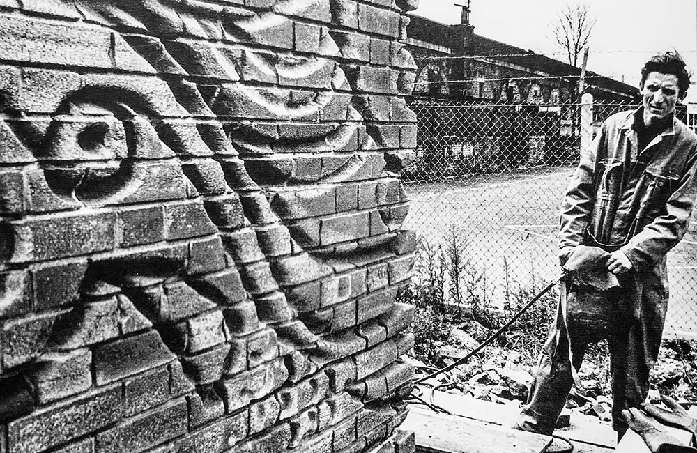 Black and white image of Bill Mitchell inspection his artwork