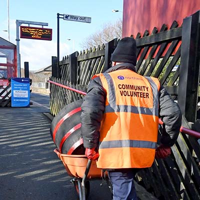 Community volunteer wheeling barrow up to platform