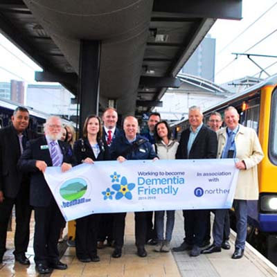 Members of Bentham Dementia Friendly Charity Displaying banner on station platform