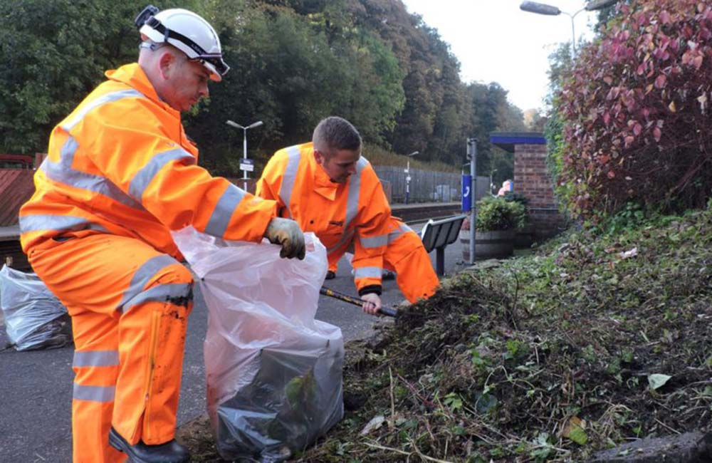 Two community rail volunteers cleaning up garden area