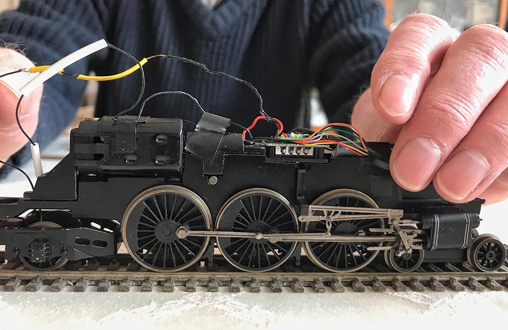 A man examines the electrics and wiring of a model steam engine.